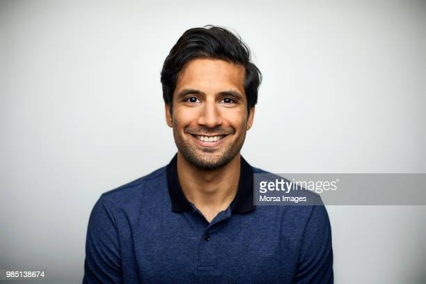 portrait of smiling mid adult man wearing t-shirt - glimlachen stockfoto's en -beelden