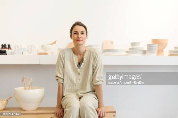 portrait of smiling mid adult potter sitting in workshop - potter stock pictures, royalty-free photos & images