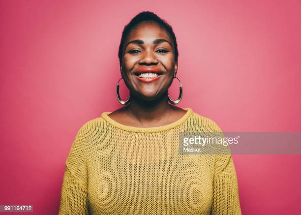 Portrait of smiling mid adult woman against pink background