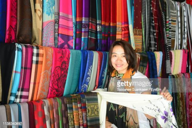 portrait of smiling mid adult woman buying scarfs at market - 売り出し中 ストックフォトと画像