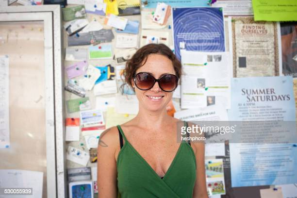 portrait of smiling mid adult woman in front of community notice board - heshphoto foto e immagini stock