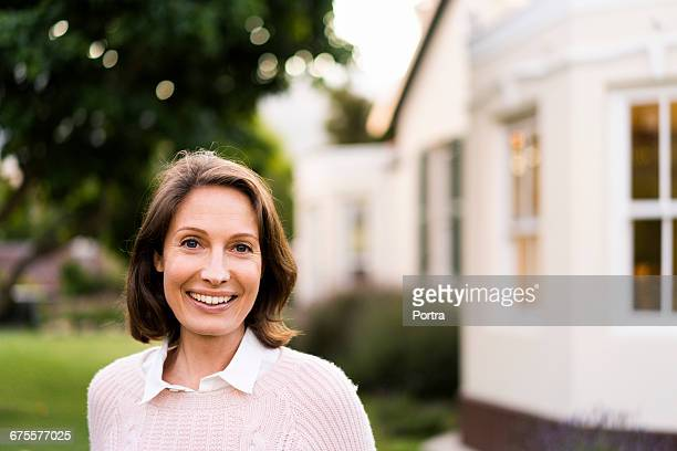 Portrait of smiling mid adult woman in yard