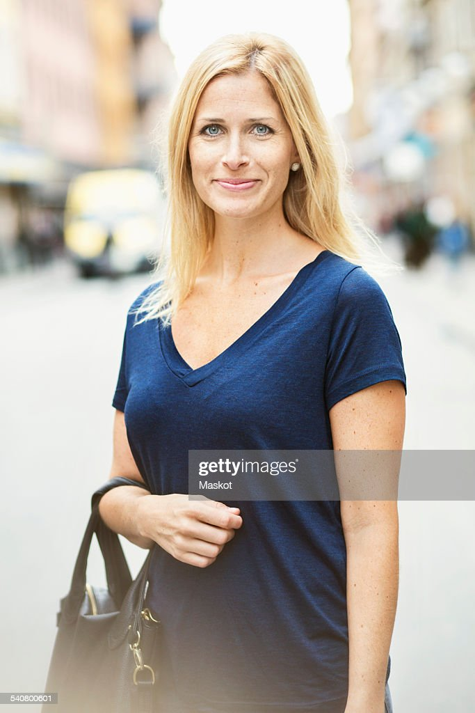 Portrait of smiling mid adult woman standing on street in city : Stock-Foto