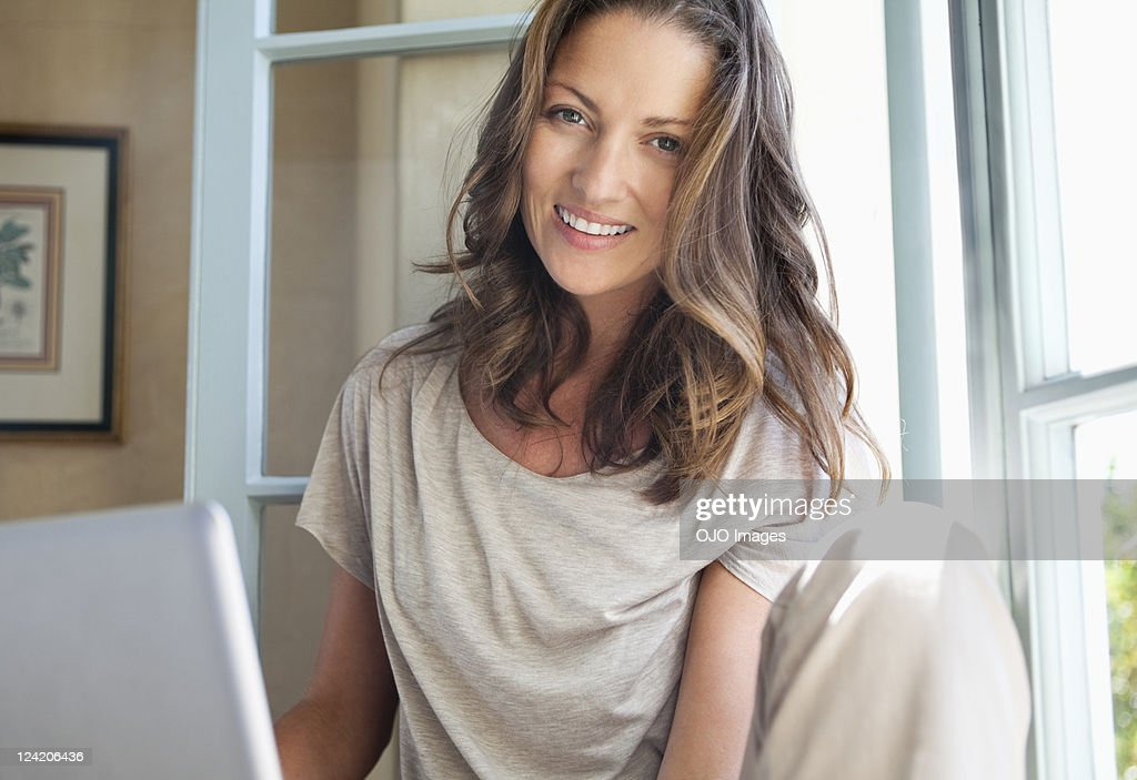 Portrait of smiling mid adult woman using laptop at home : Stock Photo