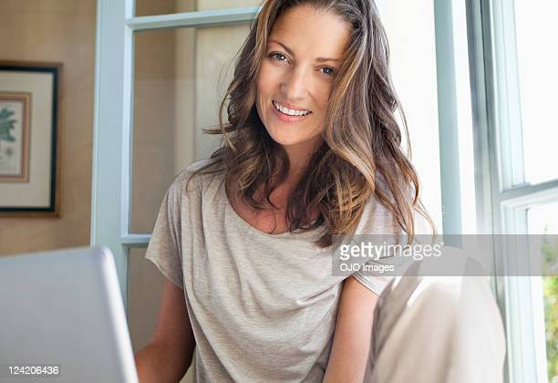 Portrait of smiling mid adult woman using laptop at home