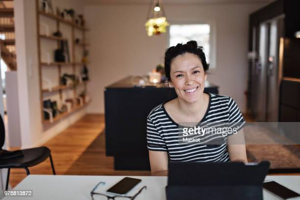 portrait of smiling mid adult woman using laptop at table in living room - 35 39 years stock pictures, royalty-free photos & images