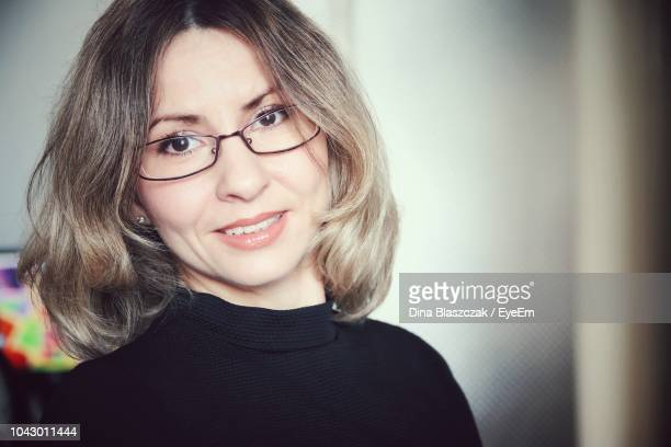 portrait of smiling mid adult woman wearing eyeglasses while standing against wall - melena mediana fotografías e imágenes de stock