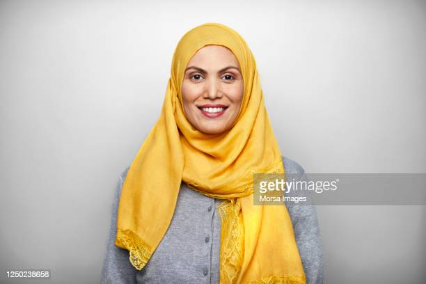 portrait of smiling mid adult woman wearing hijab. - middle east stock pictures, royalty-free photos & images