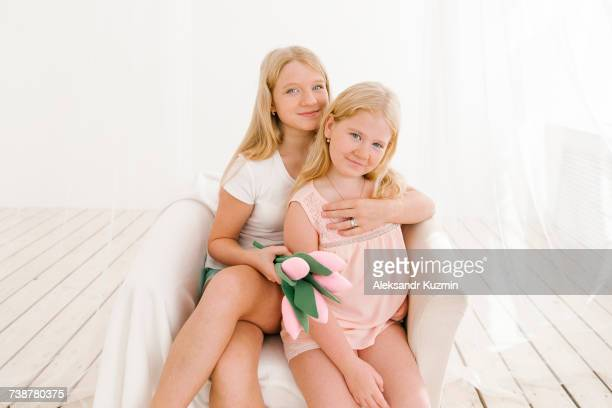 Portrait of smiling Middle Eastern sisters in armchair