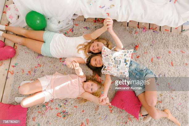 portrait of smiling middle eastern sisters laying on floor holding hands - konfetti boden stock-fotos und bilder