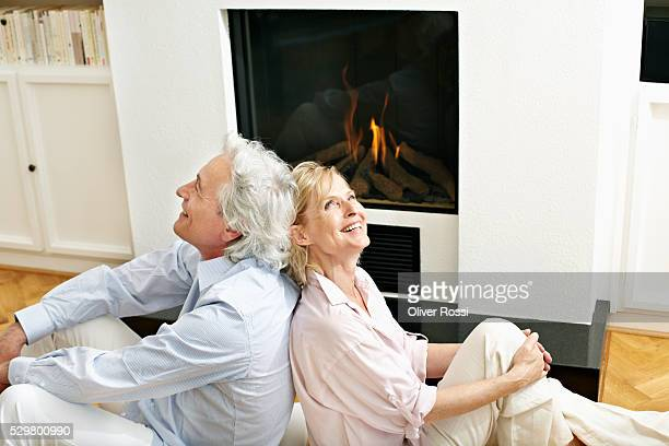 Portrait of smiling middle-aged couple sitting back to back on floor in front of fireplace