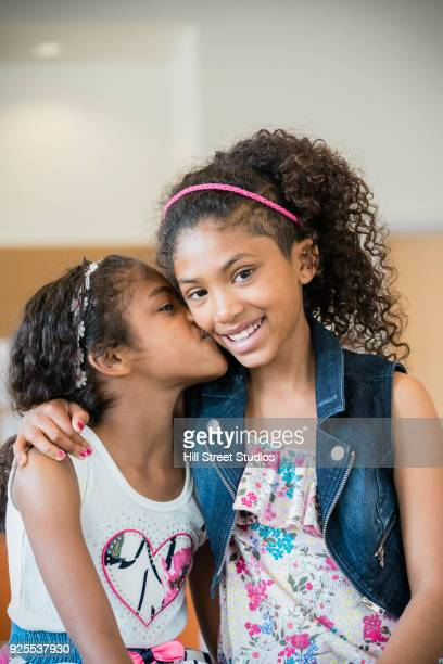 portrait of smiling mixed race girl kissing sister on cheek - 8 9 anni foto e immagini stock