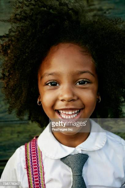 Portrait of smiling Mixed Race girl near wooden wall