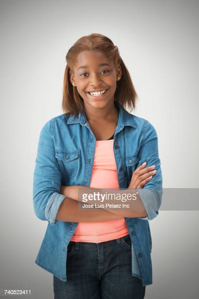 Portrait of smiling Mixed Race girl with arms crossed