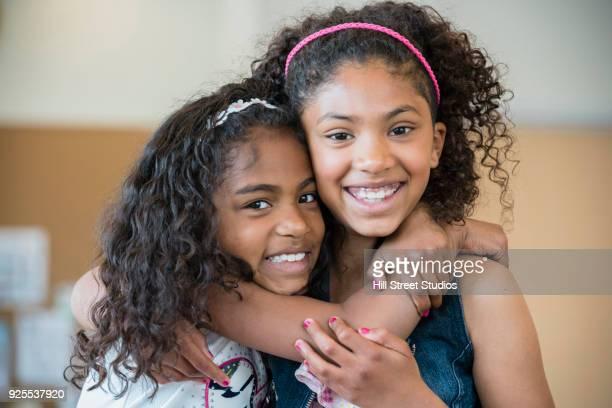 portrait of smiling mixed race girls hugging - 8 9 anni foto e immagini stock