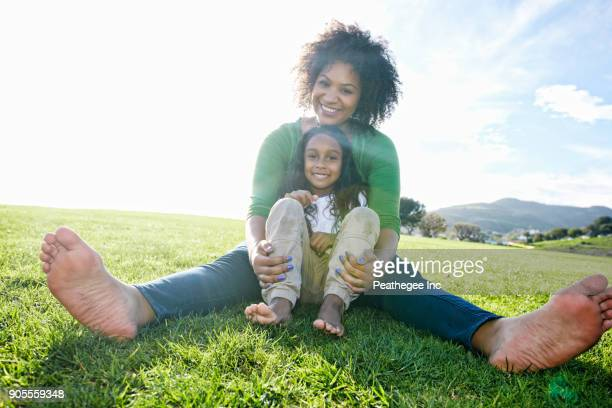 Portrait of smiling mixed race mother and daughter sitting in grass