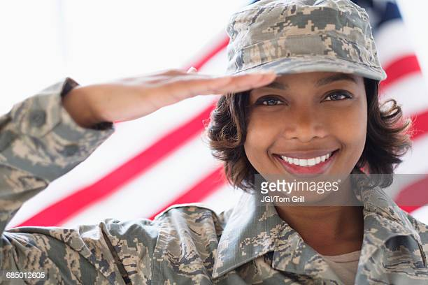 Portrait of smiling Mixed Race soldier saluting near American flag
