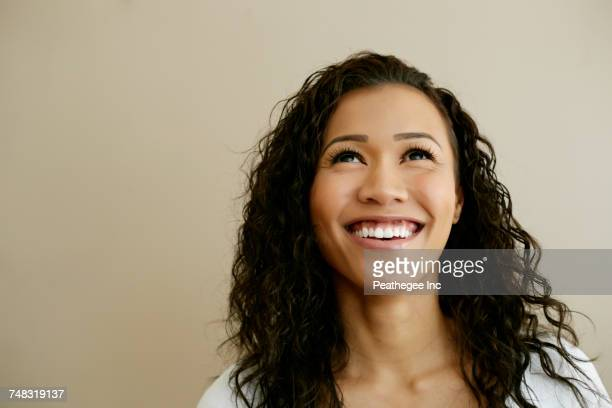 Portrait of smiling Mixed Race woman looking up