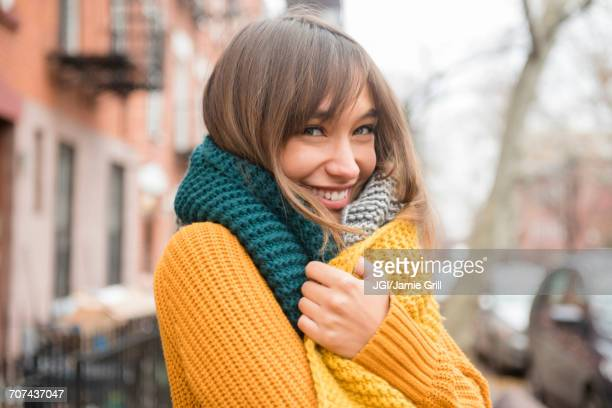 portrait of smiling mixed race woman wearing scarf in city - kälte stock-fotos und bilder
