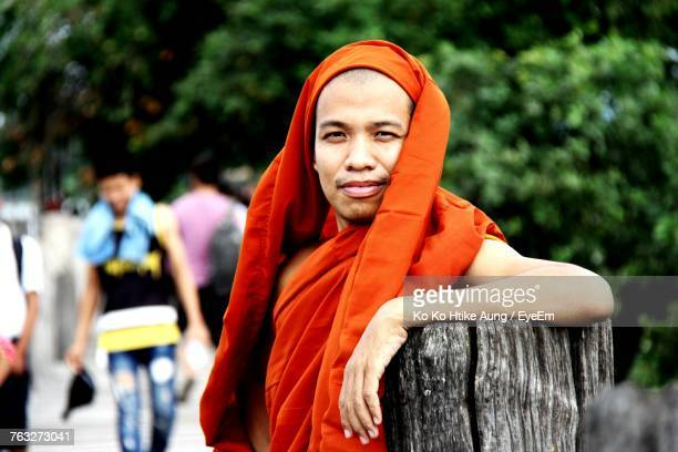 portrait of smiling monk leaning on wooden post - ko ko htike aung stock pictures, royalty-free photos & images