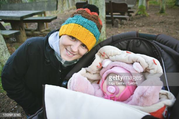 portrait of smiling mother and baby at park - liga cerina stock pictures, royalty-free photos & images