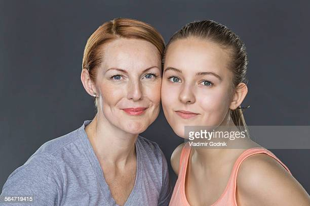 Portrait of smiling mother and daughter against gray background