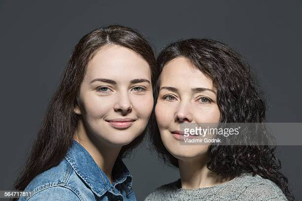 portrait of smiling mother and daughter against over gray background - familia de dos generaciones fotografías e imágenes de stock