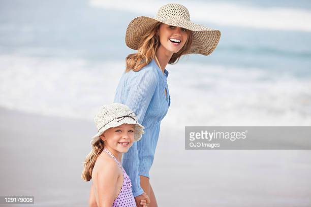 portrait of smiling mother and daughter at beach - sun hat stock pictures, royalty-free photos & images