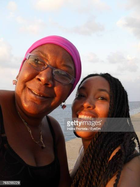 Portrait Of Smiling Mother And Daughter At Beach
