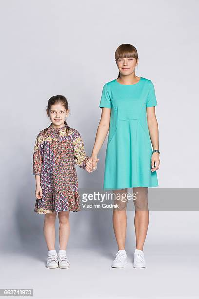 Portrait of smiling mother and daughter holding hands against white background