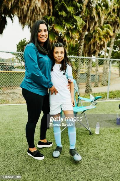 portrait of smiling mother and daughter on sidelines after soccer game - fußballtrikot stock-fotos und bilder