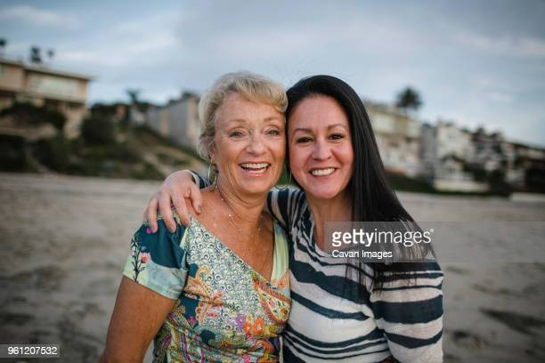portrait of smiling mother and daughter standing at beach against sky during sunset - carlsbad california stock pictures, royalty-free photos & images
