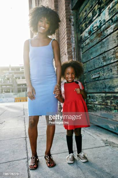 portrait of smiling mother and daughter standing on sidewalk - jolie fille photos et images de collection