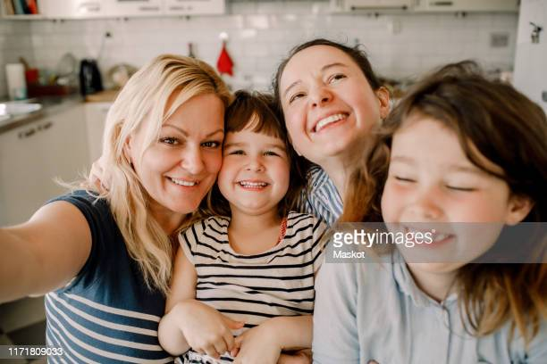 portrait of smiling mother and daughters at home - lgbtq  and female domestic life fotografías e imágenes de stock