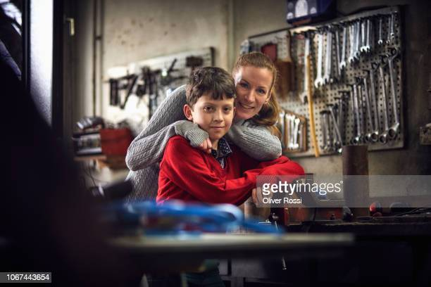portrait of smiling mother and son in a workshop - pre adolescent child stock pictures, royalty-free photos & images