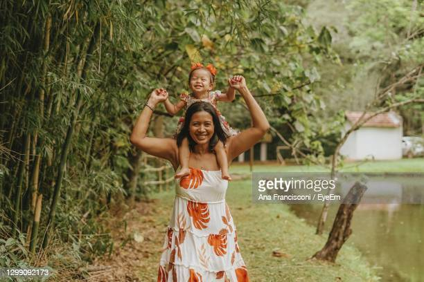 portrait of smiling mother carrying daughter on shoulder by pond at park - south america stock pictures, royalty-free photos & images