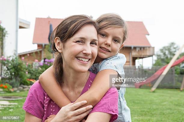 Portrait of smiling mother carrying daughter piggyback in garden