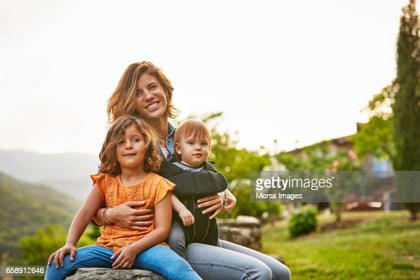 portrait of smiling mother carrying kids at yard - famiglia con due figli foto e immagini stock