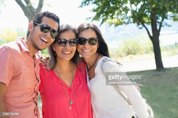 Portrait of smiling mother posing with son and daughter in park