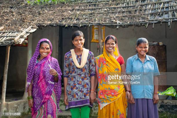 portrait of smiling mothers and daughters standing outside house in village - village stock pictures, royalty-free photos & images