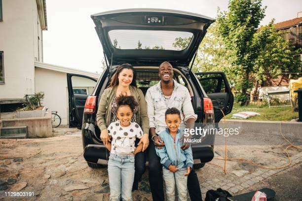 portrait of smiling multi-ethnic family leaning on car trunk in front yard - landvoertuig stockfoto's en -beelden