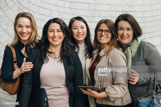 portrait of smiling multi-ethnic female business professionals standing against wall at workplace - frauenpower stock-fotos und bilder
