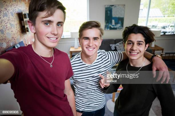 portrait of smiling multi-ethnic friends taking selfie while standing at home - fugitive stock photos and pictures
