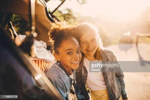 portrait of smiling multi-ethnic girls in car trunk during picnic - 6 7 anni foto e immagini stock