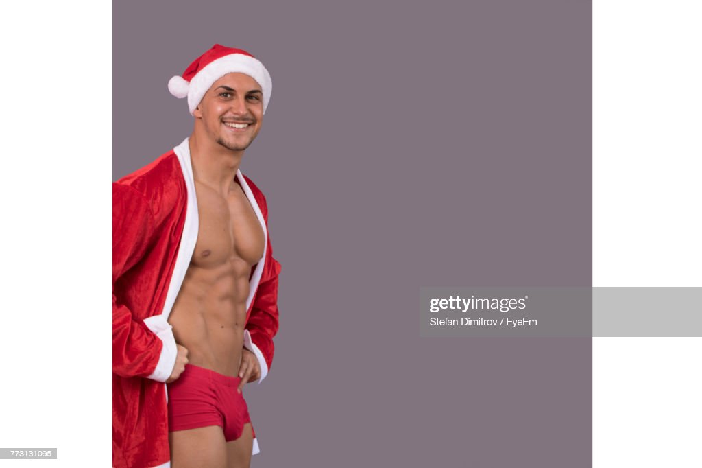Portrait Of Smiling Muscular Man Wearing Santa Hat While Standing Against Gray Background : Photo