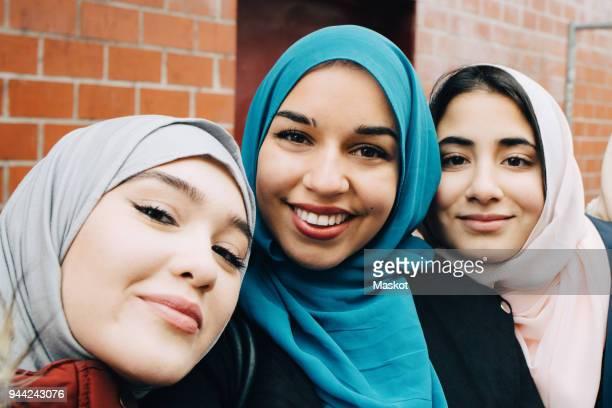 Portrait of smiling Muslim female friends against building in city