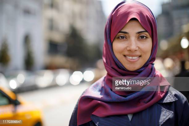 portrait of smiling muslim woman in the city - damircudic stock photos and pictures