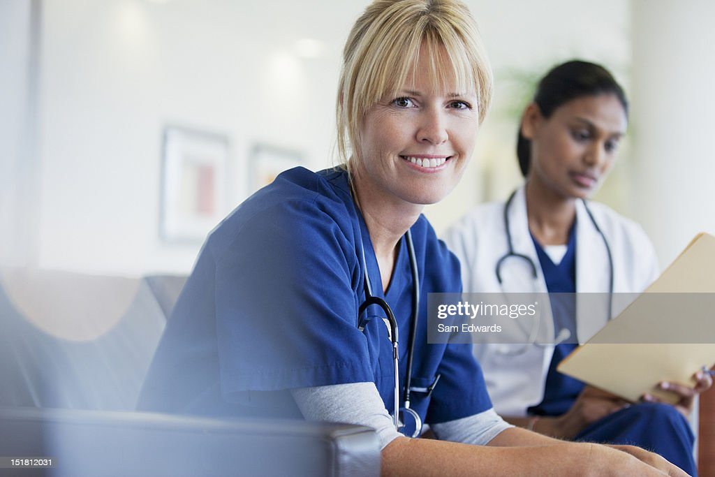 Portrait of smiling nurse sitting with doctor in hospital : Stock Photo