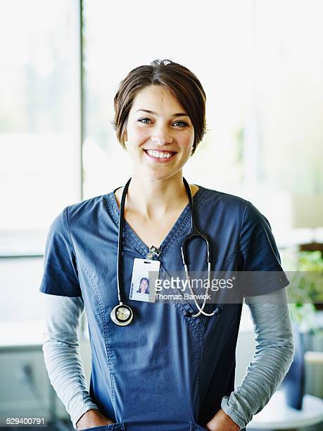 portrait of smiling nurse standing in hospital - 看護師 ストックフォトと画像