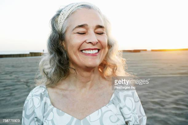 portrait of smiling older caucasian woman at beach - 60 64 years stock pictures, royalty-free photos & images